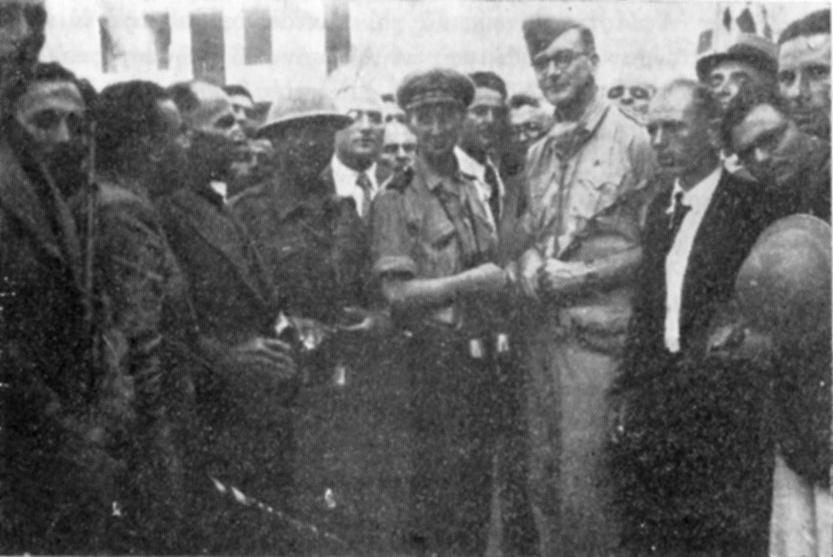 Η άφιξης των συμμαχικών δυνάμεων. Διακρίνονται ο πλοίαρχος Ντέννις, ο λοχ. κ. Γιανναρόπουλος εν μέσω των ενόπλων δυνάμεων.